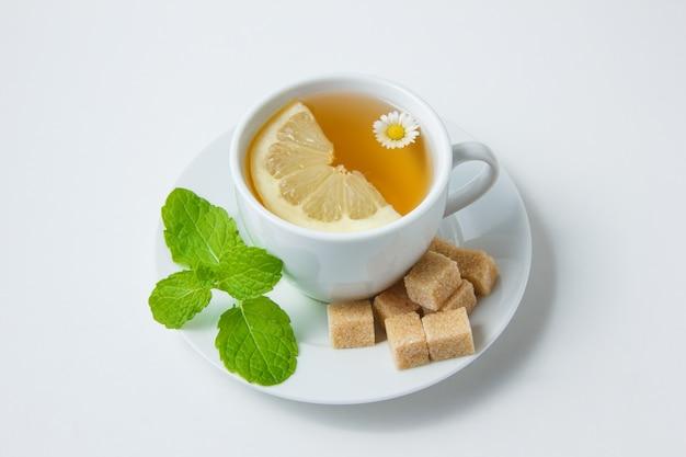 Wysoki Kąt Widzenia Filiżankę Herbaty Rumiankowej Z Cytryną, Liśćmi Mięty, Cukrem Na Białej Powierzchni. Poziomy Darmowe Zdjęcia