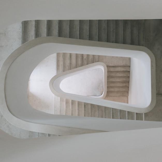 Wysoki Kąt Widzenia Nowoczesnych Spiralnych Schodów Na Wystawie Pod światłami Darmowe Zdjęcia