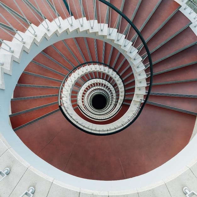 Wysoki Kąt Widzenia Nowoczesnych Spiralnych Schodów Pod światłami Darmowe Zdjęcia