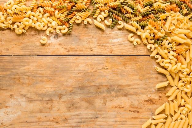 Wysoki kąt widzenia różnych rodzajów niegotowanego makaronu na drewnianym biurku Darmowe Zdjęcia