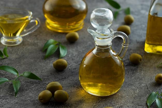 Wysoki widok butelki wypełniał oliwa z oliwek na marmurowym tle Darmowe Zdjęcia