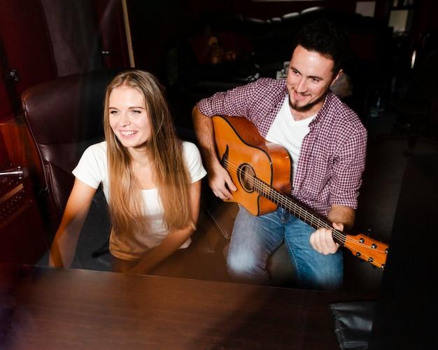 Wysoki Widok Mężczyzna Gra Na Gitarze I Kobieta Uśmiecha Się Darmowe Zdjęcia