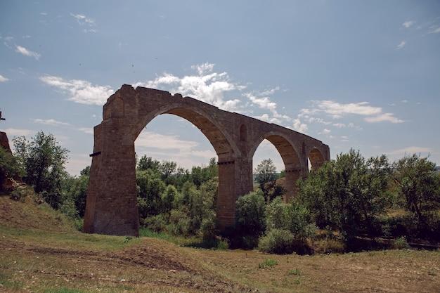 Wysoki Zrujnowany Kamienny Most Stoi Latem Na Polu Nad Rzeką Premium Zdjęcia