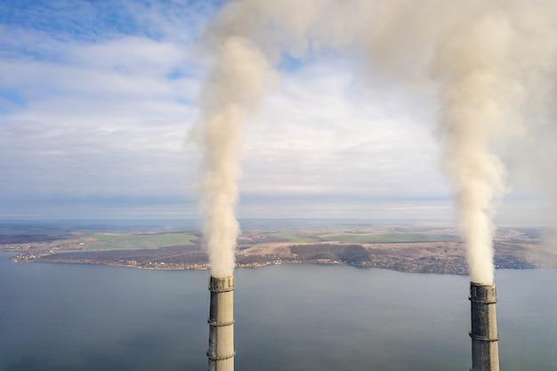 Wysokie drymby elektrownia, bielu dym na wiejskim krajobrazie, jezioro woda i niebieskie niebo kopia, interliniują tło. Premium Zdjęcia