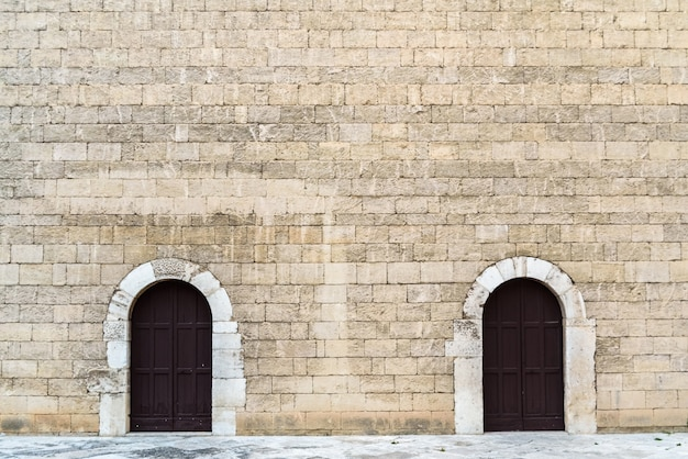 Wysokie kamienne ściany z dwoma symetrycznymi drzwiami, średniowieczne kamienne tło. Premium Zdjęcia