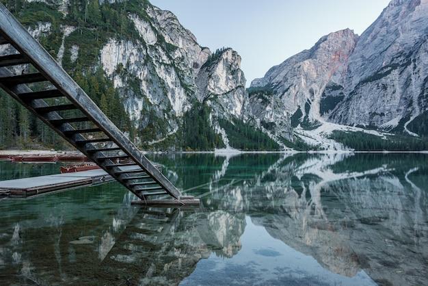 Wysokie Skaliste Góry Odbijały W Braies Jeziorze Z Drewnianymi Schodkami Blisko Mola W Włochy Darmowe Zdjęcia