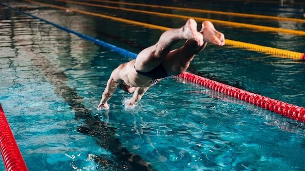 Wysokiego kąta męski pływak nurkuje w basenie Darmowe Zdjęcia