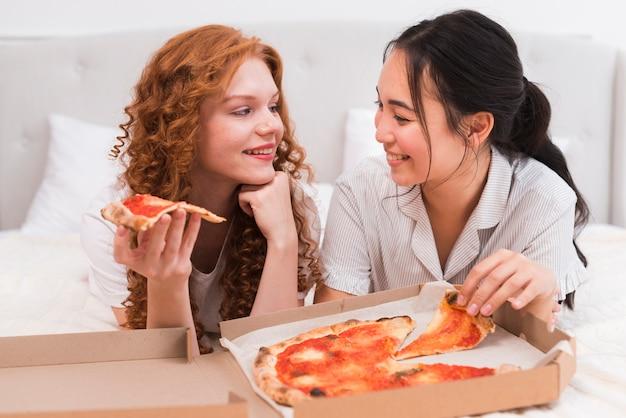 Wysokiego kąta smiley kobiety je pizzę Darmowe Zdjęcia