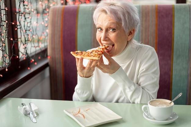 Wysokiego kąta starsza kobieta przy restauracyjnym łasowaniem Darmowe Zdjęcia