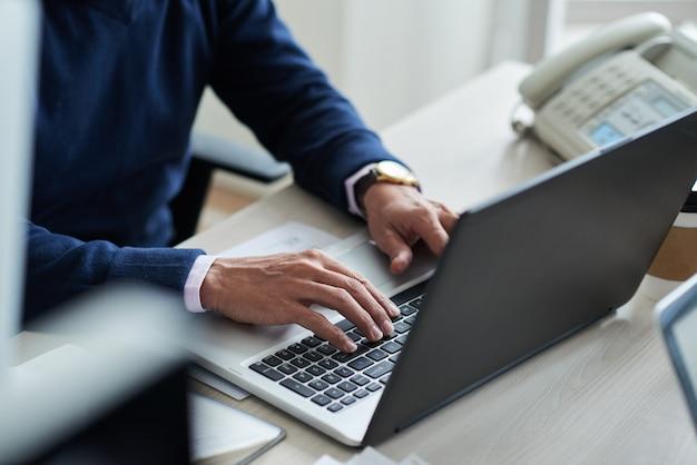 Wysokiego kąta widok cropped pracownik przy pracą z laptopem Darmowe Zdjęcia