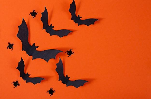 Wystrój Halloween Z Pająkami I Nietoperzami Z Czarnego Papieru Latającymi Nad Pomarańczowym Tłem Premium Zdjęcia