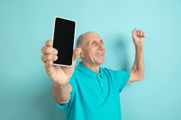 Wyświetlam Pusty Ekran Telefonu. Portret Kaukaski Starszego Mężczyzny Na Niebieskim Studio. Darmowe Zdjęcia
