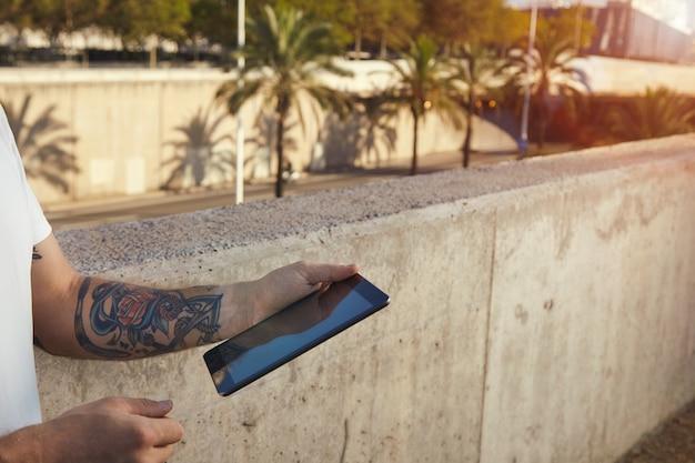 Wytatuowany Mężczyzna Trzyma Czarną Tabletkę Stojącą Obok Szarej Betonowej ściany W Krajobrazie Miasta Z Palmami Darmowe Zdjęcia