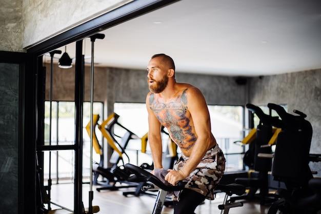 Wytatuowany, Muskularny, Brodaty Mężczyzna ćwiczy Cardio Na Rowerze W Siłowni W Pobliżu Dużego Okna Z Widokiem Na Drzewa Na Zewnątrz Darmowe Zdjęcia