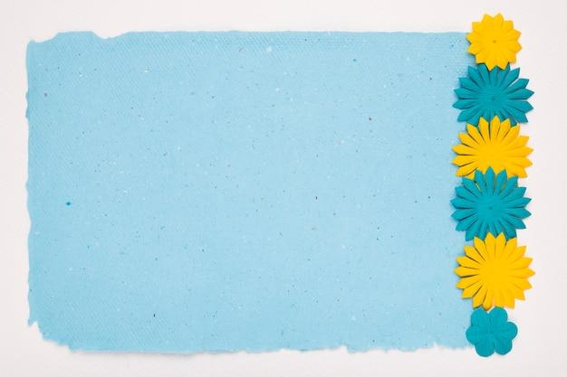 Wytnij obramowanie kwiatów na niebieskim papierze na białym tle Darmowe Zdjęcia