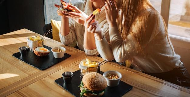 Wytnij Widok Młodych Kobiet Siedzących Przy Stole I Plotkujących. Trzymają Posiłek W Rękach. Premium Zdjęcia