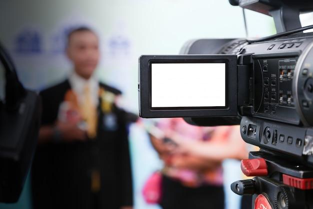 Wywiad Medialny. Zbliżenie Profesjonalnej Kamery Wideo Z Niewyraźną Osobą Vip Premium Zdjęcia