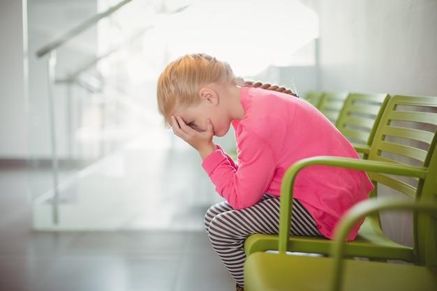 Wzburzony Dziewczyny Obsiadanie Na Krześle W Korytarzu Premium Zdjęcia