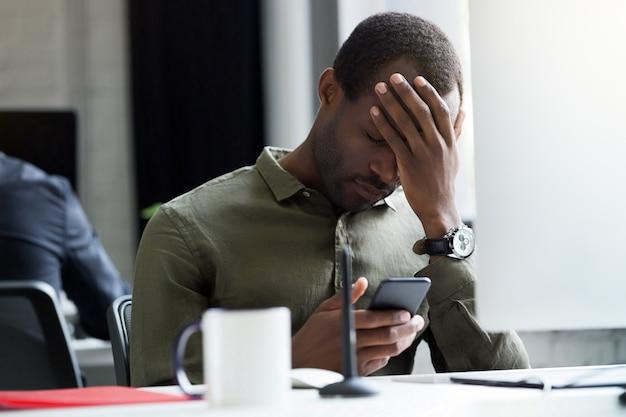 Wzburzony Młody Afrykański Mężczyzna Czytelnicza Wiadomość Na Jego Telefonie Komórkowym Darmowe Zdjęcia