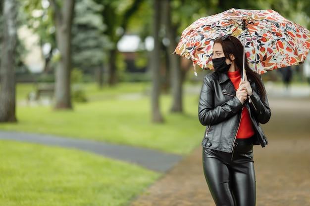 Wzdłuż Ulicy Idzie Zamaskowana Dziewczyna. Dziewczyna W Masce Ochronnej Spaceruje Po Parku Z Parasolem W Deszczu. Zakażenie Koronawirusem Covid-19 Premium Zdjęcia
