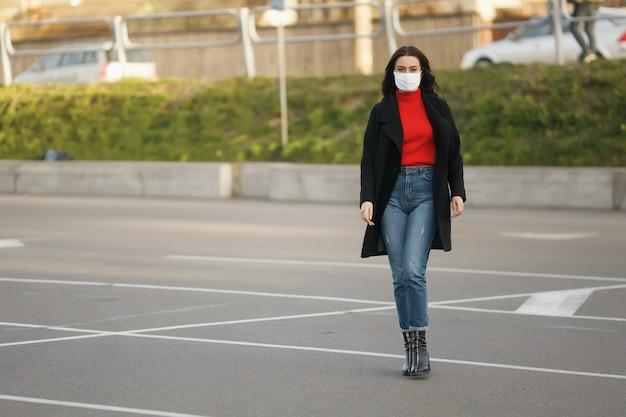 Wzdłuż Ulicy Idzie Zamaskowana Dziewczyna. Zakażenie Koronawirusem Covid-19. Premium Zdjęcia