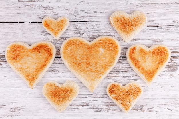 Wznoszący toast chlebowi serca wpólnie na drewnianym stole, pojęcie duża szczęśliwa rodzina Premium Zdjęcia