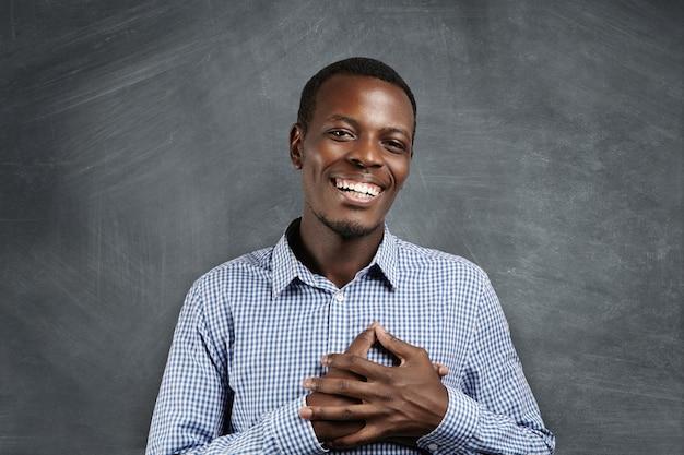 Wzruszony I Wdzięczny Afrykanin Uśmiecha Się Radośnie, Trzymając Ręce Na Piersi, Aby Wyrazić Swoją Wdzięczność I Wdzięczność. Ciemnoskóry Mężczyzna Wyglądający Na Zadowolonego Z Jakiejś Wzruszającej I Przejmującej Historii Darmowe Zdjęcia