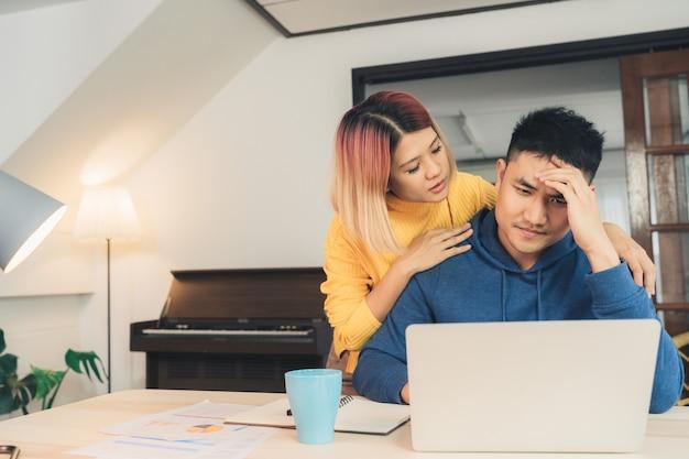 Young podkreślił para azjatyckich zarządzanie finansami, przegląd ich rachunków bankowych za pomocą komputera przenośnego Darmowe Zdjęcia