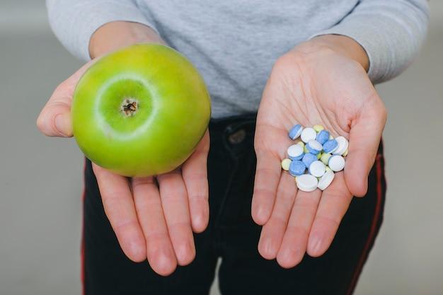 Z Góry Kobieta Uprawna Pokazująca świeże Zielone Jabłko I Stos Lekarstwa Na Dłoniach Na Szaro Premium Zdjęcia