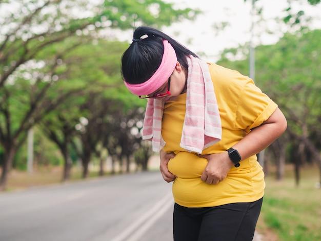 Z Nadwagą Kobieta Trzyma Jej Brzucha. Koncepcja Odchudzania Premium Zdjęcia