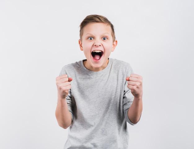 Z podnieceniem chłopiec zaciska jego pięść stoi przeciw białemu tłu Darmowe Zdjęcia