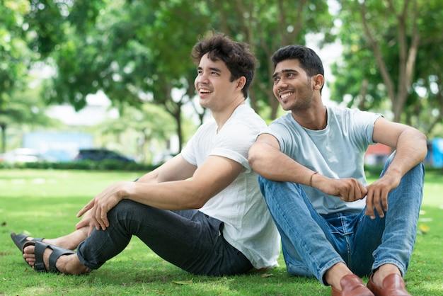 Z podnieceniem przystojni młodzi człowiecy w przypadkowej odzieży obsiadaniu na trawie Darmowe Zdjęcia