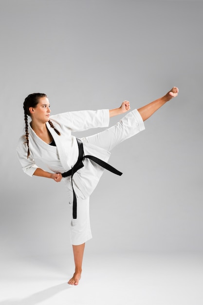 Z ukosa karate kobieta w tradycyjnym białym kimonie na białym tle Darmowe Zdjęcia