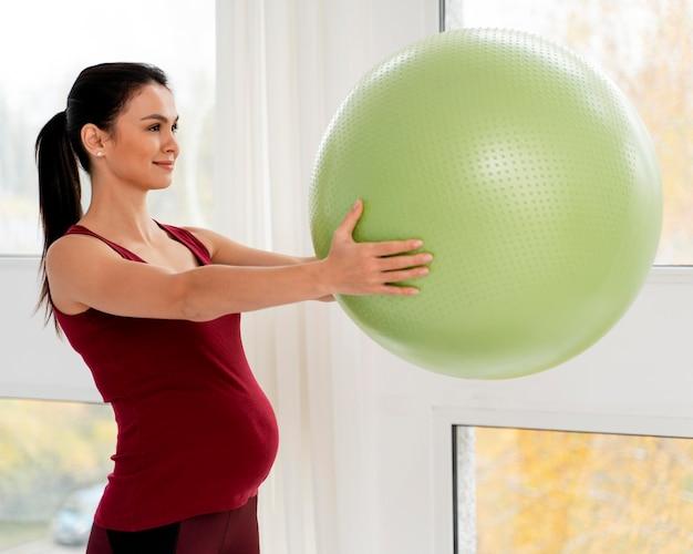 Z Ukosa Kobieta W Ciąży Trzyma Zieloną Piłkę Fitness Darmowe Zdjęcia
