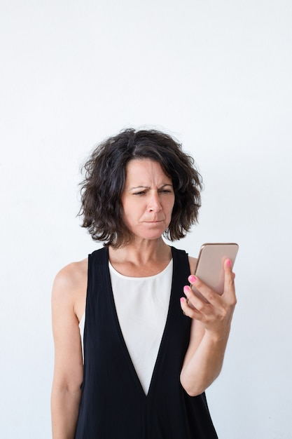 Zaakcentowana nieszczęśliwa kobieta z smartphone dostaje zły nowy Darmowe Zdjęcia