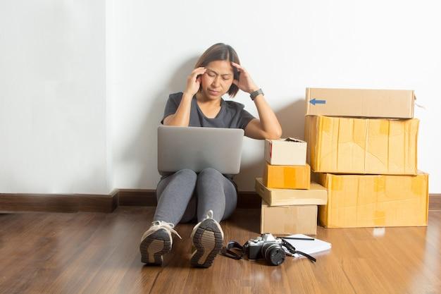 Zaakcentowane kobiety siedzi przy pracującym laptopem od pokoju domu Premium Zdjęcia