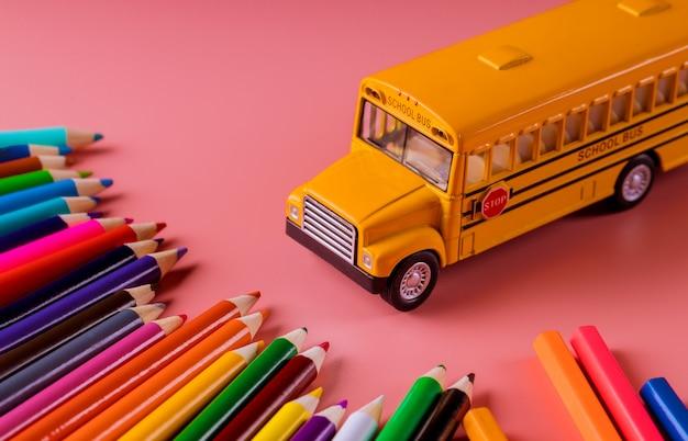 Zabawkarski autobus szkolny z kolorów ołówkami na różowym tle. Premium Zdjęcia