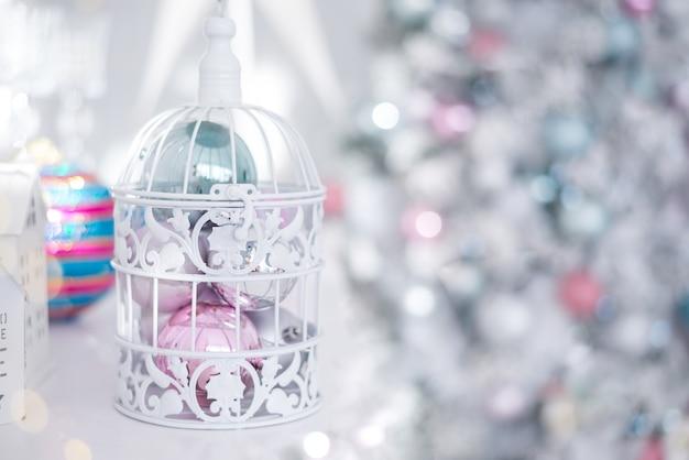 Zabawki świąteczne bombki srebrno-niebieski różowy w białej ażurowej klatce na tle lampek choinkowych. Premium Zdjęcia