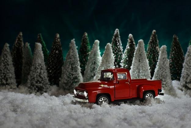 Zabawkowa czerwona furgonetka chevrolet niesie choinkę w lesie Premium Zdjęcia