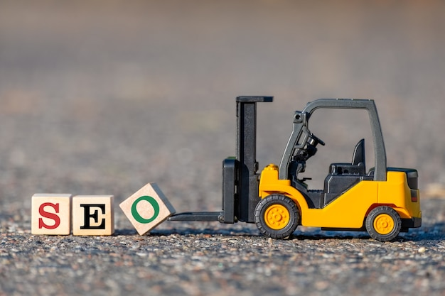 Zabawkowy Wózek Widłowy Podnosi Klocek Z Literą O, Aby Zakończyć Słowo Seo (skrót Optymalizacji Pod Kątem Wyszukiwarek) Z Asfaltu. Premium Zdjęcia