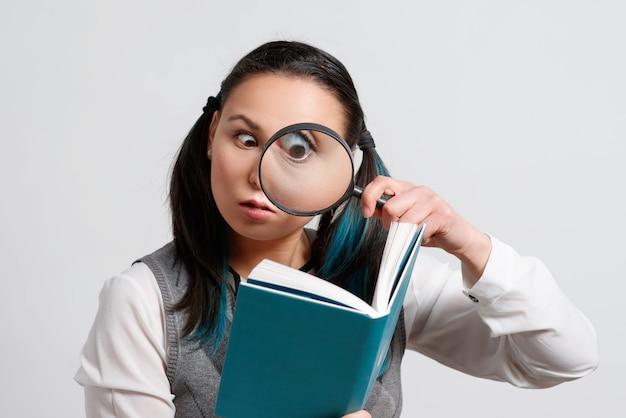 Zabawna Dziewczyna Patrząc Na Książkę Przez Szkło Powiększające Premium Zdjęcia