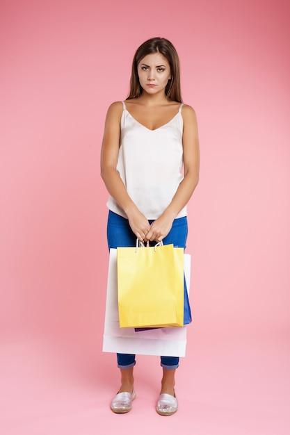 Zabawna Dziewczyna Wygląda Smutno, Trzymając Kilka Toreb Po Zakupach Darmowe Zdjęcia