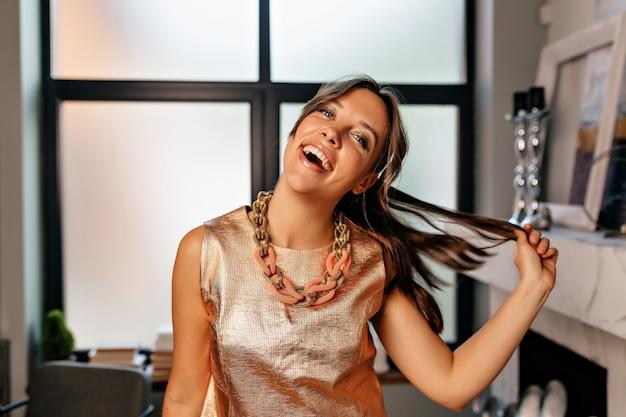 Zabawna Dziewczyna Z Szczęśliwymi Emocjami Ubrana W Połyskliwą Koszulkę I Złoty Naszyjnik Darmowe Zdjęcia