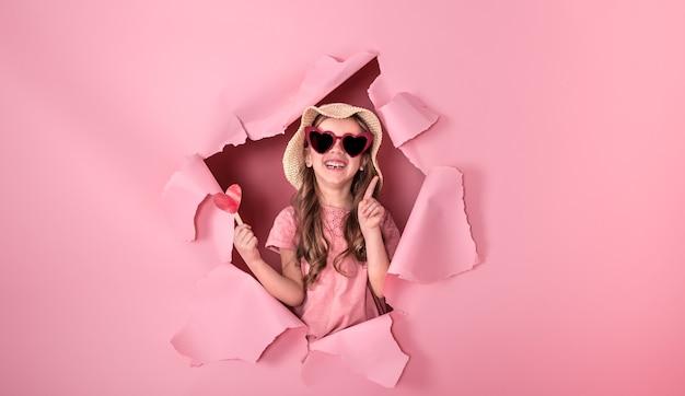 Zabawna Dziewczynka Wygląda Z Dziury W Plażowym Kapeluszu I Okularach W Kształcie Serca, Trzymająca Serduszko Na Patyku, Na Kolorowym Tle, Miejsce Na Tekst, Strzelanie Studyjne Darmowe Zdjęcia