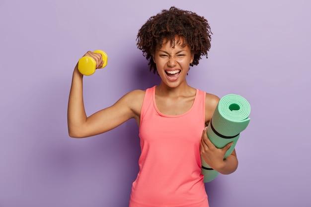 Zabawna Szczęśliwa Ciemnoskóra Kobieta Podnosi Rękę Z Hantlami, Pokazuje Bicepsy, Trzyma Zwiniętą Matę Fitness Darmowe Zdjęcia