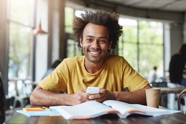 Zabawny Ciemnoskóry Mężczyzna Z Afrykańską Fryzurą Pracujący Na Papierze Kursowym, Siedząc W Kawiarni Podczas Przerwy Obiadowej, Trzymając Smartfon Z Radością Kończąc Swoją Pracę. Afrykański Facet Z Szerokim Uśmiechem W Kawiarni Darmowe Zdjęcia