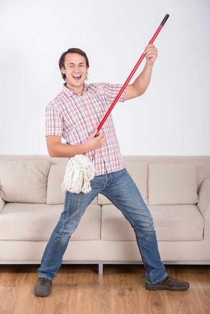 Zabawny człowiek wyciera podłogę i gra muzykę za pomocą mopa. Premium Zdjęcia