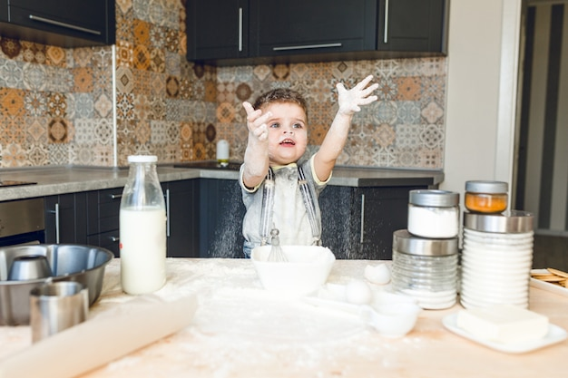 Zabawny Dzieciak Stojący W Akustycznej Kuchni, Bawiący Się Mąką I Podrzucający Ją W Powietrze. Darmowe Zdjęcia