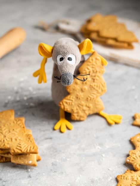 Zabawny I Uroczy Szczur Zabawkowy (symbol 2020) Z żółtymi Uszami Kradnącymi Piernikowe Ciasteczko W Kształcie Choinki, Może Służyć Jako Kartka świąteczna I Noworoczna, Zima. Premium Zdjęcia