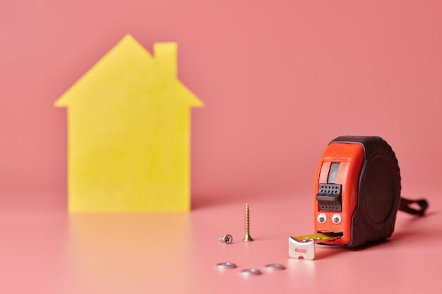 Zabawny metalowy centymetr. remont domu remont domu i odnowiona koncepcja. postać w kształcie żółtego domu na różowo. Premium Zdjęcia